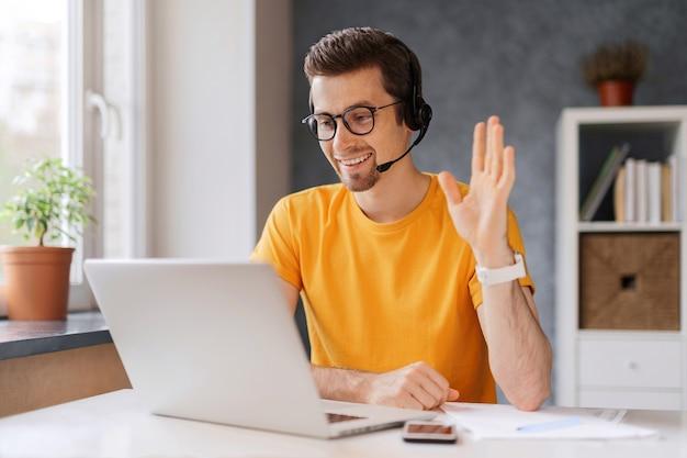 Man met headset, les starten, laptopscherm kijken, zwaaiende hand, tutor begroeten, heeft online les via videogesprek