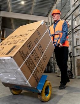 Man met helm dragende dozen