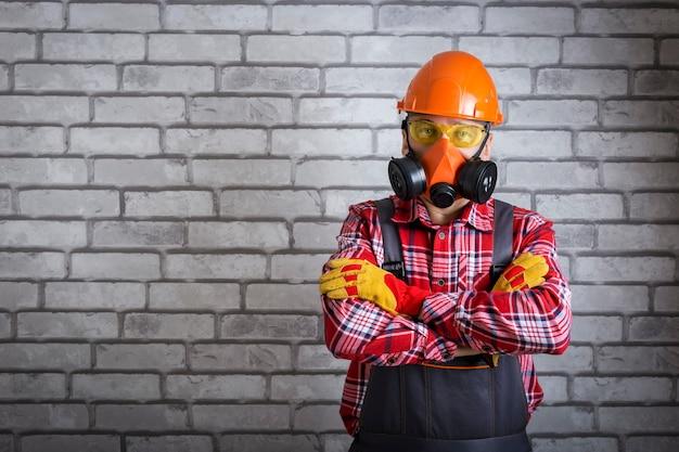 Man met helm, handschoenen bril, beschermende kleding in de buurt van bakstenen muur met kopieerruimte. werk veiligheid.