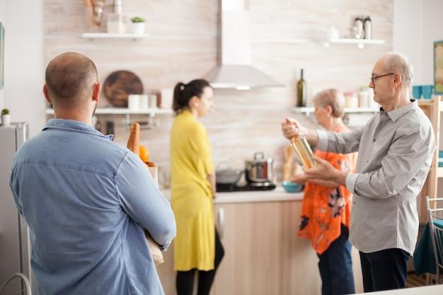 Man met herbruikbare tas uit supermarkt met boodschappen in huiskeuken voor heerlijke lunch. senior man met fles wijn.