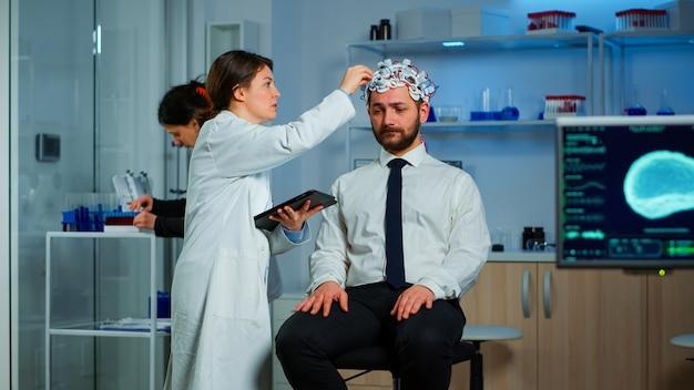 Man met hersengolf scanning headset die een professionele arts bezoekt die disfuncties van het zenuwstelsel behandelt. patiënt zit in hersenonderzoekslaboratorium terwijl neuroloogwetenschapper het eeg-apparaat aanpast