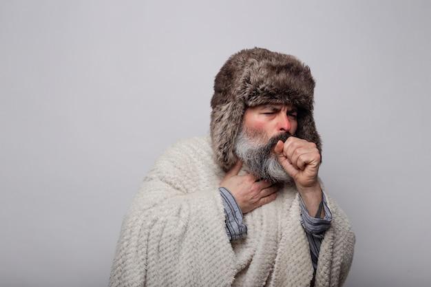 Man met hoed en deken met keelpijn hoesten