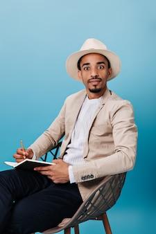 Man met hoed en jas kijkt verbaasd naar de camera en houdt een notitieboekje vast