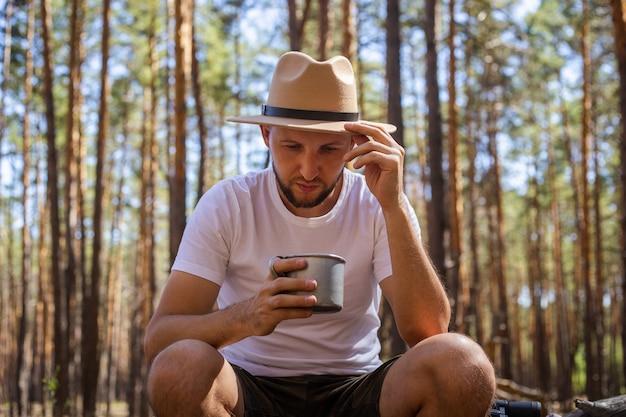 Man met hoed houdt een mok hete thee vast tijdens een kampeertrip. wandeling in de bergen, bos.
