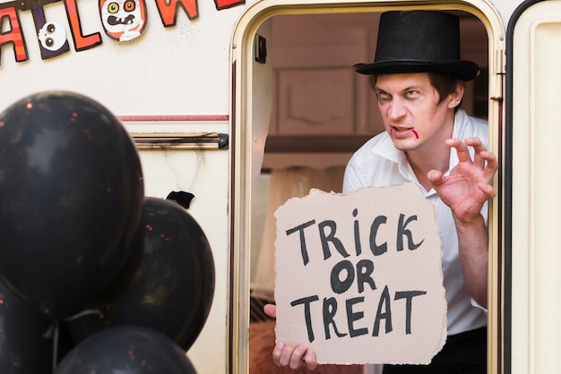 Man met hoed met trick or treat-teken