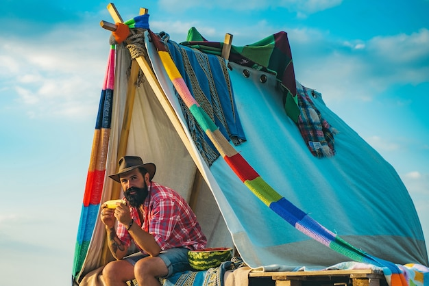Man met hoed zittend in een tent