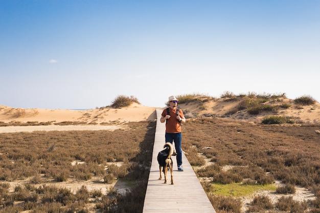 Man met hond die op het houten pad op het strand loopt en in de verte van de oceaan kijkt.
