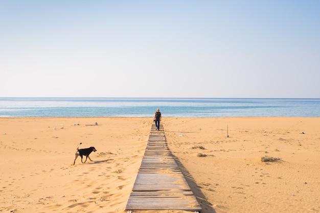 Man met hond wandelen op het tropische strand.