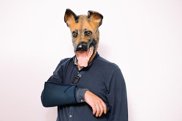 Man met hondenmasker en arm in een draagdoek wegens blessure