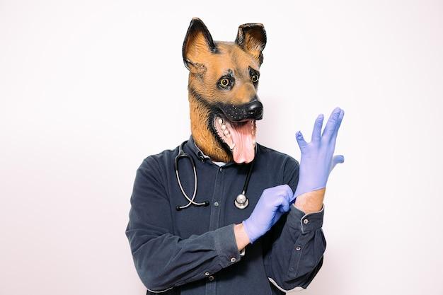 Man met hondenmasker en een stethoscoop die handschoenen draagt