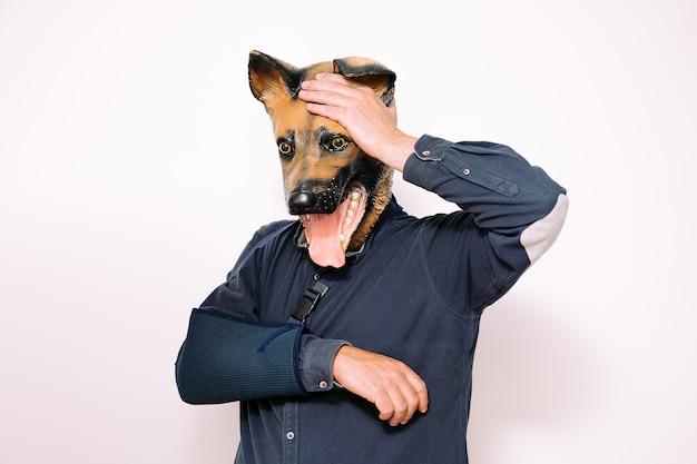Man met hondenmasker en gewonde arm in een mitella