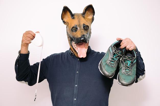 Man met hondenmasker met hardloopschoenen en riem
