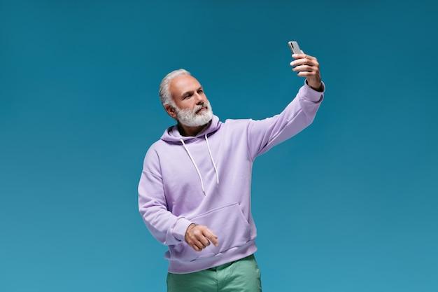 Man met hoodie maakt selfie op blauwe muur