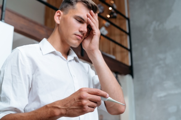 Man met hoofdpijn houdt een digitale thermometer vast