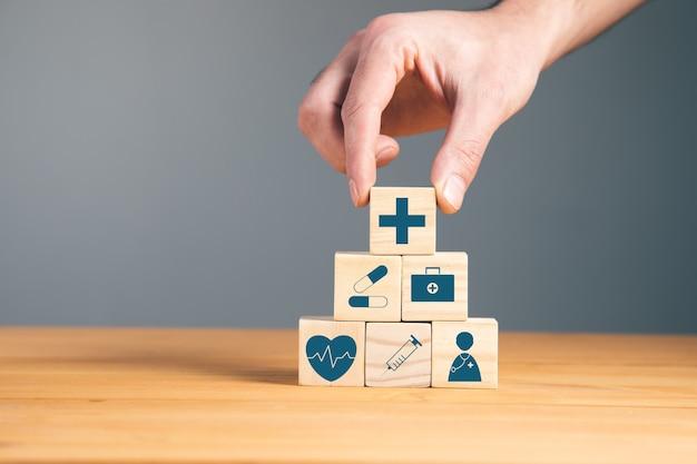 Man met houten blokken met het medische symbool van de gezondheidszorg
