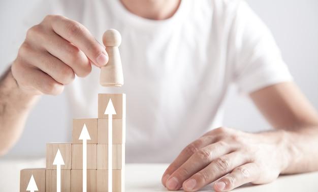 Man met houten menselijke figuur. pijlen op houten kubussen. persoonlijke ontwikkeling en carrière