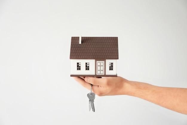 Man met huismodel en sleutel op grijs. hypotheekconcept