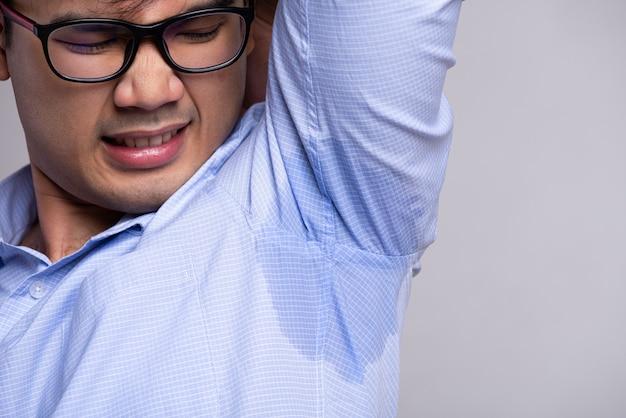 Man met hyperhidrose zweten op zijn kleren. gezondheidszorg concept.