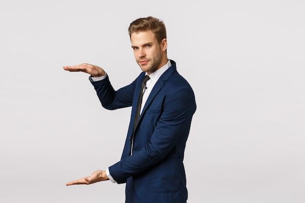 Man met iets groots. aantrekkelijke bebaarde blonde zakenman in klassieke pak, hand vasthouden als iets vast te houden, vormgeven van groot object, diagram, bedrag tonen kan winnen, witte muur
