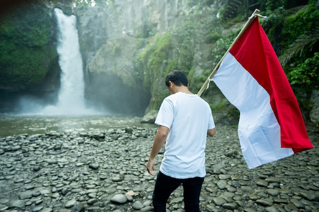Man met indonesische vlag van indonesië in waterval met prachtig uitzicht
