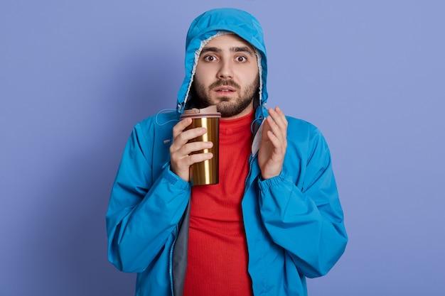 Man met jasje en rood shirt koffie drinken tegen blauwe muur, camera kijken met verbaasde gezichtsuitdrukking