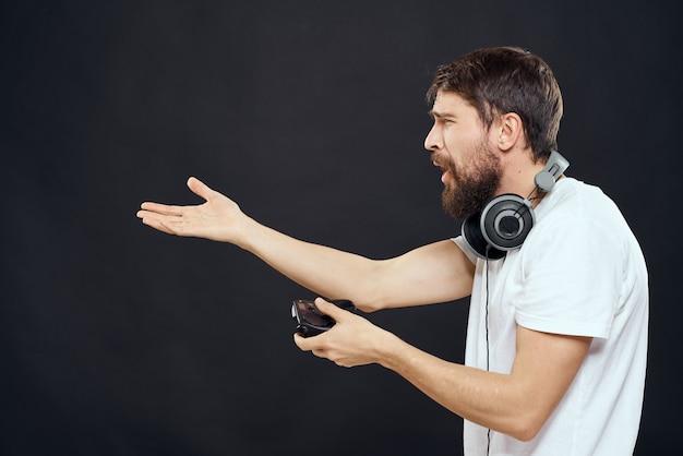 Man met joystick in handen koptelefoon technologie vrijetijdsspel levensstijl donker