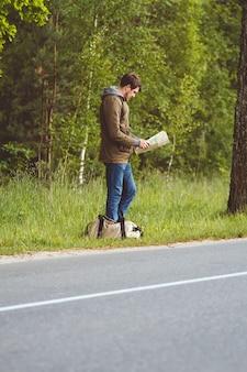 Man met kaart en tas in de hand lopen langs de weg