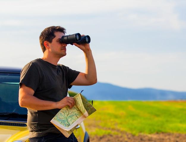 Man met kaart en verrekijker op platteland