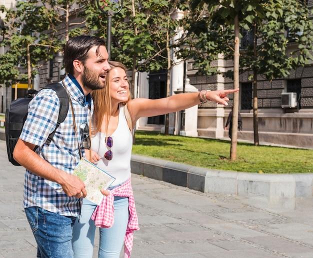 Man met kaart kijken naar gelukkige vrouw wijst naar iets Gratis Foto