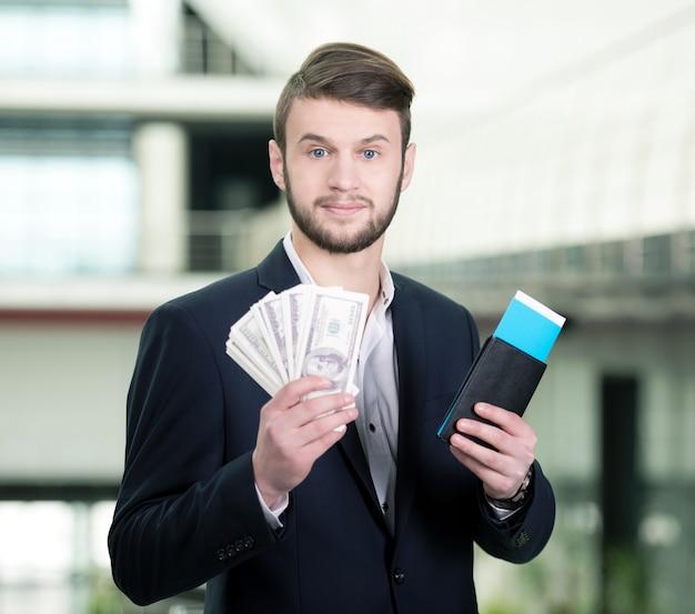 Man met kaartjes op de luchthaven om reizen te reizen.