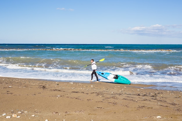 Man met kajak op zee strand