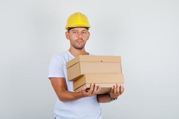 Man met kartonnen dozen in wit t-shirt, helm, vooraanzicht.