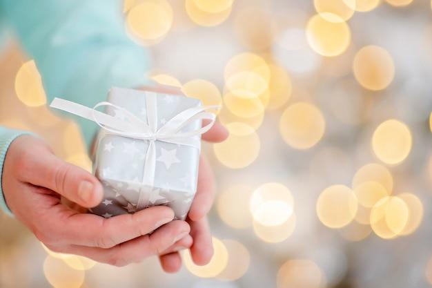Man met kerst geschenkdoos op bokeh lichten