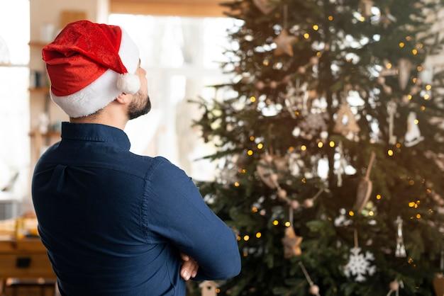 Man met kerstman kijkt naar kerstboom