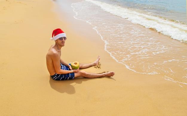 Man met kerstmuts op het strand