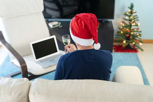 Man met kerstmuts roosteren voor de computer. concepttechnologie en opsluiting.