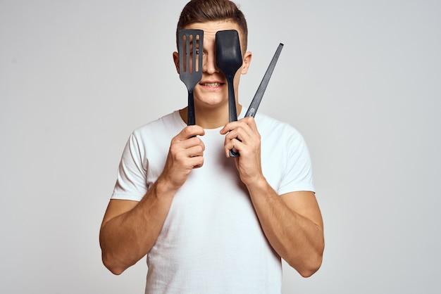 Man met keukengerei in handen op een lichte achtergrond weergave van emoties, plezier en model bijgesneden