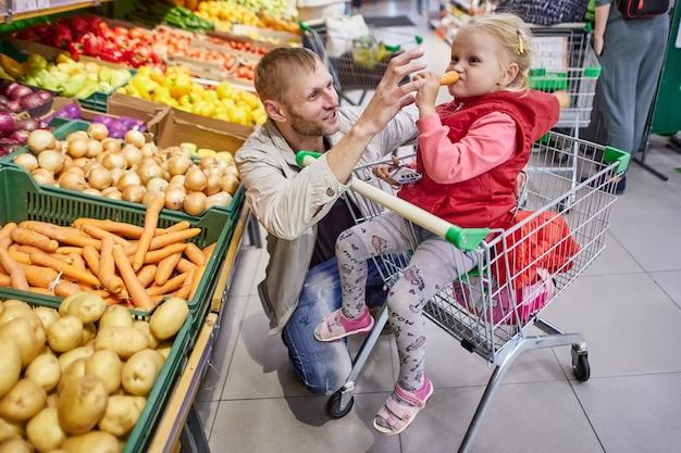 Man met kind in winkelwagentje in supermarkt
