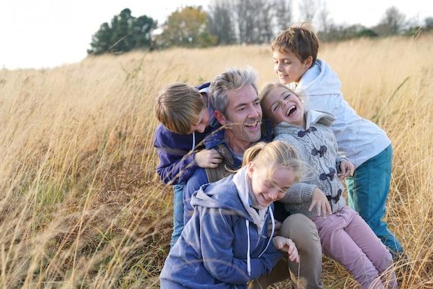 Man met kinderen spelen in het veld, op het platteland