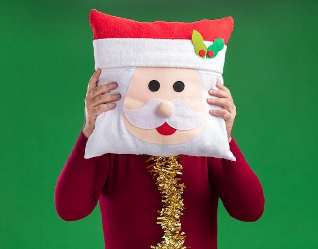 Man met klatergoud rond de nek met kerst kussen gezicht achter het verbergen staande over groene achtergrond