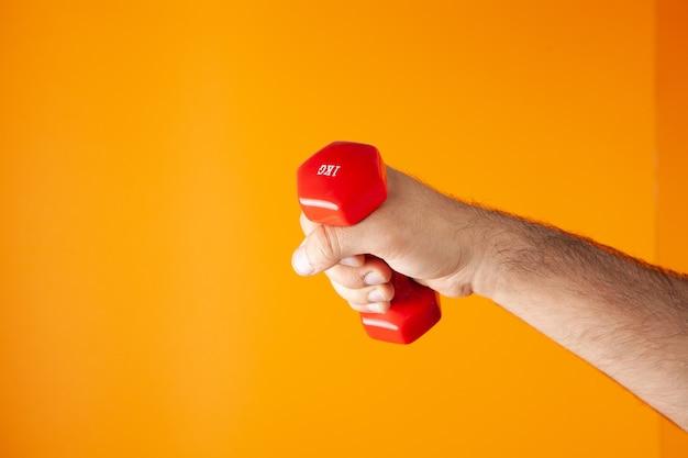 Man met kleine halters op oranje achtergrond