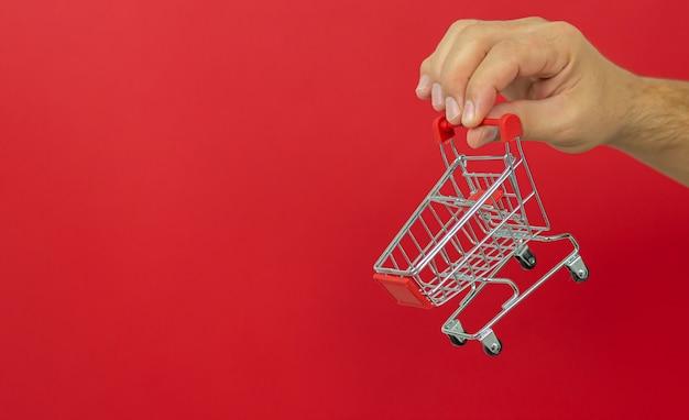 Man met kleine winkelwagen trolley op rood. online winkelen en snel leveringsconcept