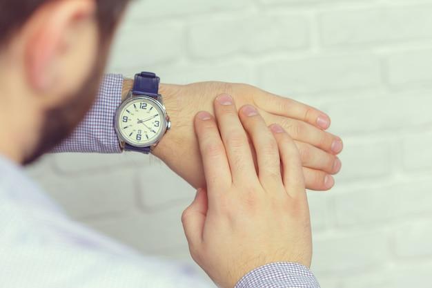 Man met klok controleert de tijd