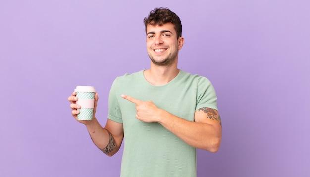 Man met koffie die vrolijk lacht, zich gelukkig voelt en naar de zijkant en naar boven wijst, een object in de kopieerruimte laat zien