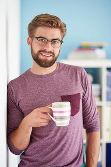 Man met koffie naast de muur