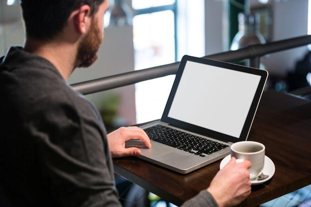 Man met koffiekopje en met behulp van laptop