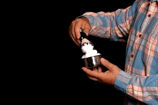Man met kom met schuim en penseel in handen voor het scheren op zwarte achtergrond