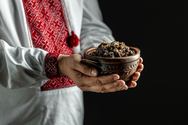 Man met kom met traditionele kutia