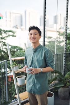 Man met kopje koffie en glimlachend op balkon