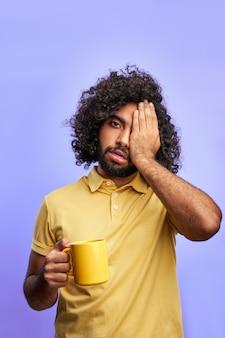 Man met kopje thee, gekrulde arabische man heeft wat slaap nodig, sluit een oog poseren op camera geïsoleerd over paarse ruimte